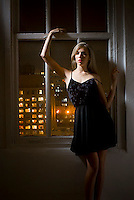 Blonde woman wearing black dress leaning against wall by window with lights of Manhattan behind her