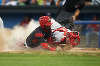 Batavia Muckdogs Marcos Rivera (8) slides under the tag of catcher Nic Perkins (43) during a game against the Auburn Doubledays on July 4, 2017 at Dwyer Stadium in Batavia, New York.  Batavia defeated Auburn 3-2.  (Mike Janes/Four Seam Images)