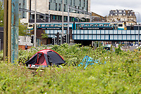 Pictured: A train travels in the background over tents on the roundabout on the junction of Callaghan Square and St Mary Street in Cardiff, Wales, UK.  Wednesday 12 June 2019<br /> Re: Homeless people living in tents in Cardiff, Wales, UK.