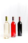 Three wine bottles on white background.  White wine, red wine, rose wine.