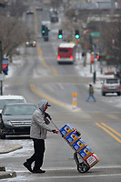 Andrew Lawrence, a delivery driver for McBride Distributing in Fayetteville, pushes a dolly loaded with beer Friday, Feb. 12, 2021, across the street while making deliveries on Dickson Street in Fayetteville. Wintry weather and below-freezing temperatures are expected to continue into next week. Visit nwaonline.com/210213Daily/ for today's photo gallery. <br /> (NWA Democrat-Gazette/Andy Shupe)