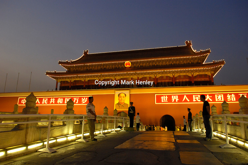 Plain clothes security and uniformed soldiers on guard at Tiananmen Gate at dusk with Mao portrait..21 Sep 2006
