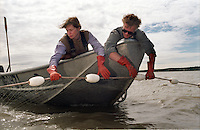 Lisa Kreb's (left) and her deckhand search an empty net for sockeye salmon at her setnet site in the Egegik River District in bristol bay, Alaska in 1998.  Bristol Bay is home to the world's largest sockeye salmon fishery.  the rivers also get a fair amount of chum, king, and chinook salmon.  Bristol bay is located in the southwest part of Alaska.  1998 saw a very poor return of salmon.