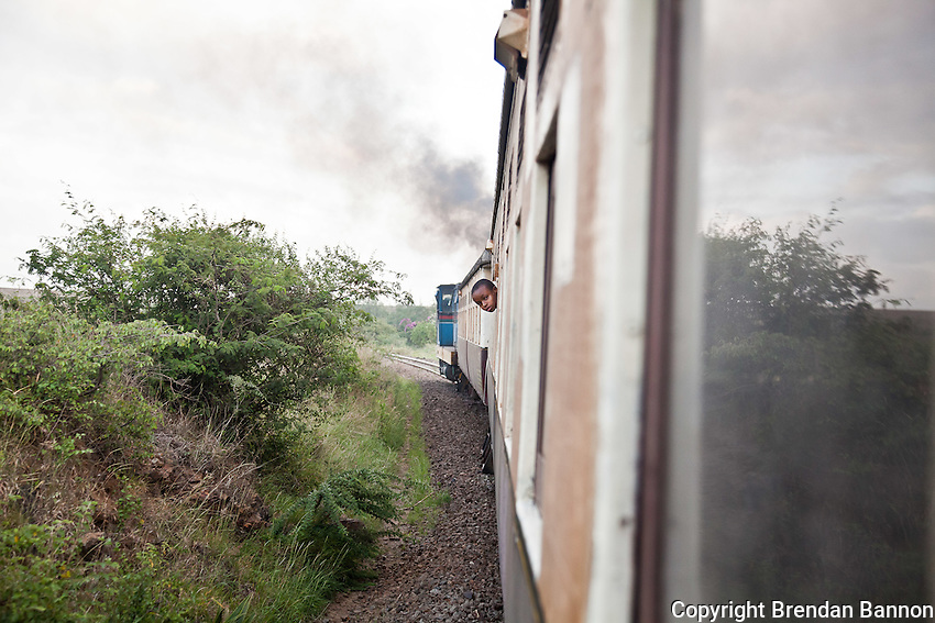 A school boy riding the 6:40 AM train from Athi River to Naiorbi wathces the landscape roll by.