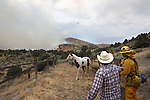 A neighbor helps round up a loose horse as firefighters battle a 150-acre fire near Holbrook Junction, Nev., on Saturday, Sept. 10, 2011. .Photo by Cathleen Allison
