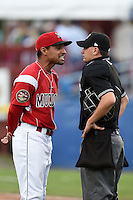 Batavia Muckdogs manager Angel Espada (4) argues a call with umpire Anthony Perez during a game against the State College Spikes on July 3, 2014 at Dwyer Stadium in Batavia, New York.  State College defeated Batavia 7-1.  (Mike Janes/Four Seam Images)