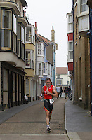 27 JUL 2013 - CROMER, GBR - Sam <br /> Kingston makes his way down a narrow side street on the run during The Anglian Triathlon in Cromer, North Norfolk, Great Britain (PHOTO COPYRIGHT © 2013 NIGEL FARROW, ALL RIGHTS RESERVED)
