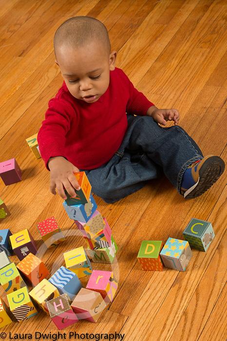 18 month old toddler boy stacking blocks making tower of 5 blocks