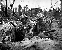 Marine Pfc. Douglas Lightheart (right) cradles his 30-cal. machine gun in his lap, while he and his buddy Pfc. Gerald Churchby take time out for a cigarette, while mopping up the enemy on Peleliu Is. September 14, 1944. Cpl. H. H. Clements. (Marine Corps)<br /> NARA FILE #:  127-N-97628<br /> WAR & CONFLICT #:  874