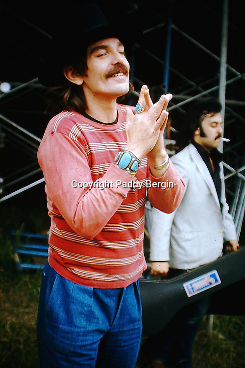 """Don Van Vliet, born Don Glen Vliet; January 15, 1941 – December 17, 2010) was an American singer, songwriter, musician and artist best known by the stage name Captain Beefheart. His musical work was conducted with a rotating ensemble of musicians called the Magic Band (1965–1982), with whom he recorded 13 studio albums. Noted for his powerful singing voice and his wide vocal range, Van Vliet also played the harmonica, saxophone and numerous other wind instruments. His music integrated blues, rock, psychedelia, and jazz with contemporary experimental composition and the avant-garde; many of his works have been classified as """"art rock."""" Beefheart was also known for often constructing myths about his life and for exercising an almost dictatorial control over his supporting musicians.<br /> <br /> An artistic prodigy in his childhood, Van Vliet later developed an eclectic musical taste during his teen years in Lancaster, California, and formed """"a mutually useful but volatile"""" friendship with musician Frank Zappa, with whom he sporadically competed and collaborated.<br /> <br /> This photo was taken at The Knebworth Festival, Hertfordshire, England in 1974 and shows guitarist Greg Davidson in the background.<br /> <br /> Here is a link to a recording of the set:<br /> https://www.youtube.com/watch?v=qmOiNnUVK-g&list=RDqmOiNnUVK-g#t=34<br /> <br /> Stock Photo by Paddy Bergin"""