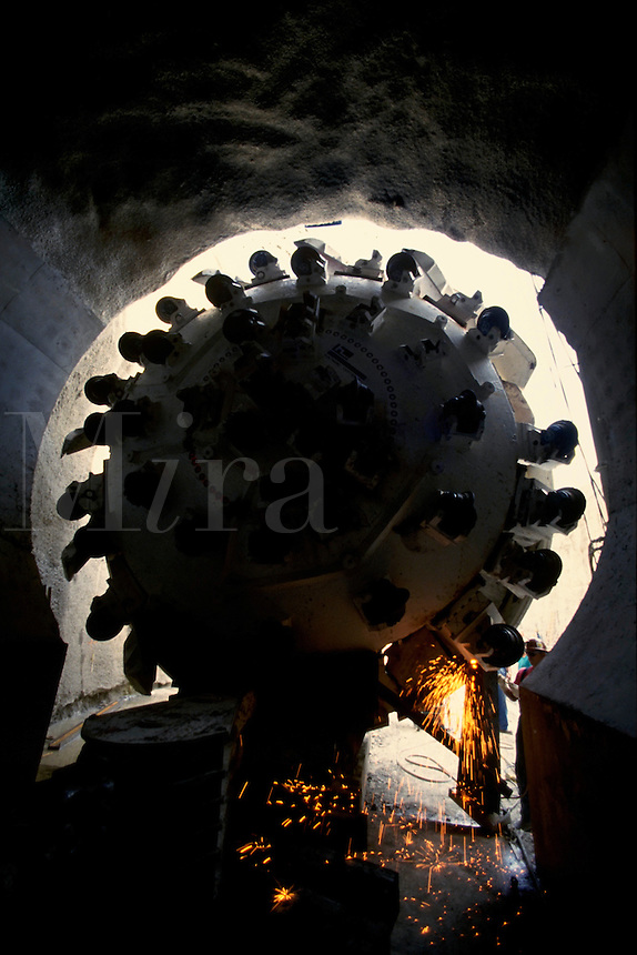 The drilling head of a tunnel boring machine is placed in the entrance of a tunnel to begin its work. A worker cuts off a support as sparks fly.