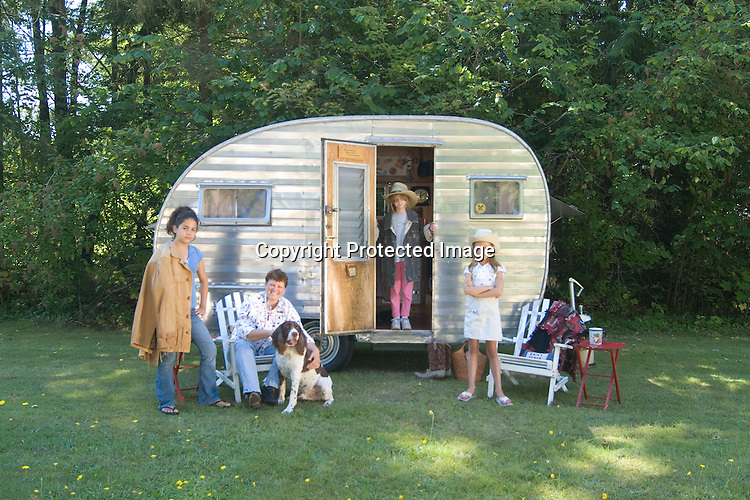 Mother and her family hanging out in front of a silver 1957 Aljo canned ham vintage travel trailer.