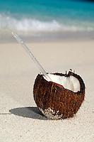 Coconut with a straw on the sand.Honeymoon Beach, St John.Virgin Islands National Park
