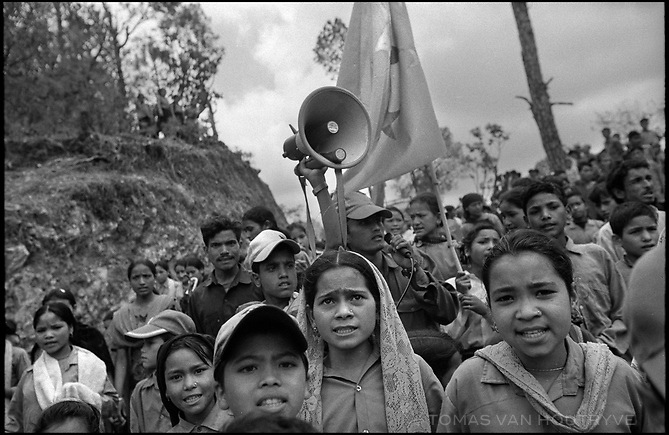 """Children are lead to march and shout Maoist slogans by rebel youth leaders at the inauguration ceremony for the Maoist rebel """"Martyr's Road,"""" celebrating the opening of the section linking the villages of Nuwagau and Tila, in Tila, Nepal on 24 June, 2005.<br />"""