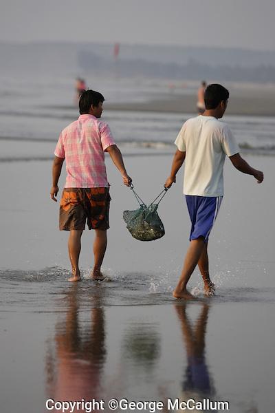 Pair of Beach fishermen carrying small catch of fish, Goa, Arabian sea, India