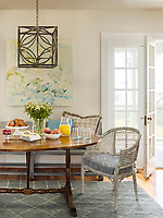 The dining room is light and airy with neutral decoration and a wood floor. The room is furnished with a traditional wood oval dining table and the dining chairs are of painted wicker. A bench seat is against one wall and there is a grey rug on the floor. A square lantern style pendant light hangs above the table.