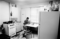 """USA. New York City. Spanish Harlem. Richie is making his school home work in the kitchen.  The Puerto Rican family lives below the poverty line and receives public assistance (AFDC, Home Relief, Supplemental Security Income and Medicaid). The family resides in units managed by the New York City Housing Authority (NYCHA) which provides housing for low income residents. NYCHA administers rental apartments in facilities, popularly known as """"projects"""". Spanish Harlem, also known as El Barrio and East Harlem, is a low income neighborhood in Harlem area. Spanish Harlem is one of the largest predominantly Latino communities in New York City. 15.09.86 © 1986 Didier Ruef ."""