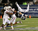 Nevada's Kendall Brock gets upended by Fresno State defenders Karl Mickelsen (43) and Derron Smith (13) during the first half of an NCAA college football game in Reno, Nev., on Saturday, Nov. 22, 2014. (AP Photo/Cathleen Allison)