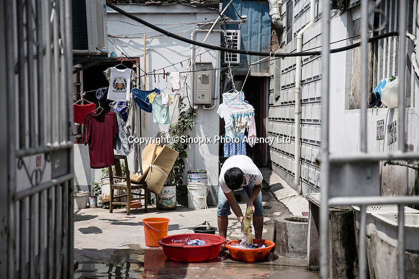 A man washes his clothes in his courtyard in Xingxing village on the outskirts of Shanghai,  China on 14 August 2015.  As China's sputtering economy has beginning to affect employment, many migrants who used to live in the village to work on Shanghai's numerous construction sites and factories are beginning to thin out.