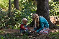 Mädchen spielt mit Kleinkind, Kind im Wald mit Stöcken und Zapfen