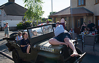 A man poses on a WW2 Jeep at a street  party in Welling, Kent, England 8th May 2020. Victory in Europe (VE) 75th Anniversary Celebrations during the UK Lockdown due to the Coronavirus pandemic. Photo by Alan Stanford / PRiME Media Images