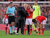 Wales physiotherapists see to Joe Allen (C) who suffered a suspected head injury during the FIFA World Cup Qualifier Group D match between Wales and Republic of Ireland at The Cardiff City Stadium, Wales, UK. Monday 09 October 2017