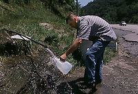 Residents in the area of Delbarton fill water jugs from water flowing out a pipe on the side of the highway. They believe their water at home is tainted from toxic sludge from coal mines and that this water is pure to drink.
