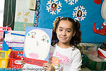 Education Elementary school Grade 2 girl holding up self portrait of self as president art activity social studies horizontal