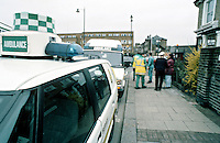 Paramedic ambulance crews and police officers attend a road traffic accident. The policeman is talking to a witness.