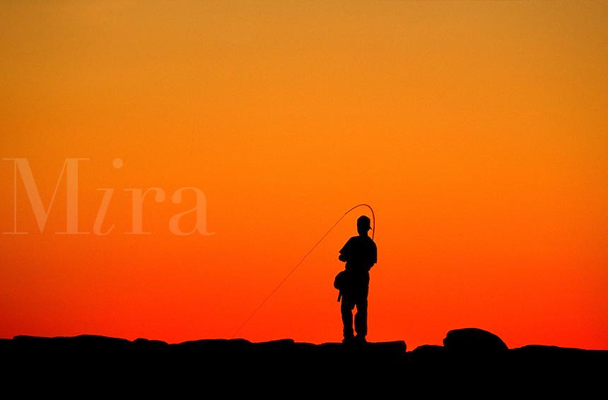 Boy fishing from a jetty at sunset, Menemsha, Martha's Vineeyard