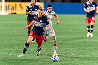 FOXBOROUGH, MA - OCTOBER 7: Adam Buksa #9 of New England Revolution on the attack as Jonathan Osorio #21 of Toronto FC closes during a game between Toronto FC and New England Revolution at Gillette Stadium on October 7, 2020 in Foxborough, Massachusetts.