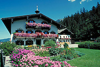 Spring flowers grace traditional style Bavarian building. Austria Europe.