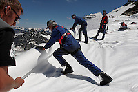 "Workers wrap Brunnenkogel Ferner with a fleece-like cover to keep it from melting.  Rolls of the material are attached it to the top of the part of the glacier to help save the ski industry since the glacier is retreating.  <br /> Brunnenkogel Ferner--(Austrian word for glacier )is being wrapped with a fleece-like cover to keep it from melting.  Workers unwrapped rolls of the material and attached it to the top of the part of the glacier.  The parts covered melt slower than if not covered. The ski area at 3,400 meters is covered by the thirteen workers to help save the ski industry since the glacier is retreating.  The cost of materials is one Euro per square meter...The Alpine glaciers -- in Austria, Switzerland, France and Italy -- are losing one percent of their mass every year and, even supposing no acceleration in that rate, will have all but disappeared by the end of the century...More hot, dry summers like that of 2003 in Europe, when the loss speeded to five percent, could cut the life expectancy to no more than 50 years, according to Wilfried Haeberli of the University of Zurich...""We estimate that by the end of the 21st century, with a medium-type climate scenario, about five percent of what existed in the 1970s will have survived, he added."