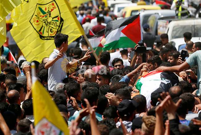 Palestinians carry the body of Shadi al-Shurafa who was killed by Israeli army fire on July 27 and his body was returned today, during a funeral procession in Beita village in the West Bank, on August 10, 2021. Photo by Shadi Jarar'ah