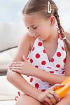USA, Florida, St. Petersburg, Girl (10-11) applying sun lotion on arm