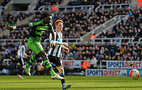 Bafetibis Gomis of Swansea City (left) shoots at goal during the Barclays Premier League match between Newcastle United and Swansea City played at St. James' Park, Newcastle upon Tyne, on the 16th April 2016