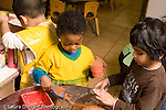 Preschool Headstart 3-5 year olds sand table two boys playing as boy paints in background horizontal