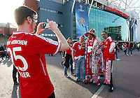 A Bayern Munich fan covered in scarves is photographed outside Old Trafford, home stadium of Manchester United before the game