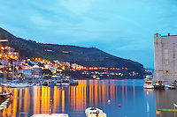 The old harbour with evening city light reflections in the water, Saint John's Fort to the right in evening blue light Dubrovnik, old city. Dalmatian Coast, Croatia, Europe.