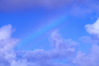 Heavenly photo of a rainbow crossing a light blue sky with soft fluffy clouds.