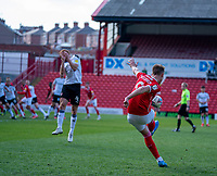 24th April 2021, Oakwell Stadium, Barnsley, Yorkshire, England; English Football League Championship Football, Barnsley FC versus Rotherham United; Cauley Woodrow of Barnsley crosses as Shaun MacDonald of Rotherham protects his face
