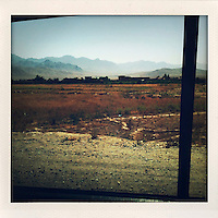 On the outskirts of Kabul a group of buildings appear among roadside scrubland that gives way to mountains rising from the horizon.