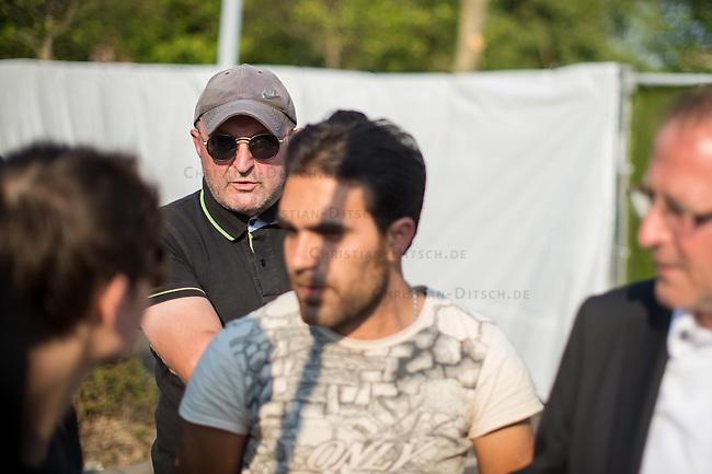 """Nach den pogromartigen Ausschreitungen gegen eine Fluechtlinsunterkunft im saechschen Heidenau am Freitag den 21. August 2015 durch Anwohnerinnen der Ortschaft, kamen am Samstag de 22. August 2015 ca. 250 Menschen in die Ortschaft um ihre Solidaritaet mit den Gefluechteten zu zeigen.<br /> Am Vorabend hatten Rassisten, Nazis und Hooligans sich zum Teil Strassenschlachten mit der Polizei geliefert um zu verhindern, dass Fluechtlinge in einen umgebauten Baumarkt einziehen. Ueber 30 Polizisten wurden dabei verletzt.<br /> Bis in die Abendstunden des 22. August blieb es trotz spuerbarer Anspannung um die Unterkunft ruhig. Im Laufe des Tages wurden immer wieder Gefluechtete mit Reisebussen gebracht was von den wartenenden Heidenauern mit Buh-Rufen begleitet wurde. Vereinzelt wurde auch """"Sieg Heil"""" gerufen, was die Polizei jedoch nicht verfolgte.<br /> Kurz vor 23 Uhr griffen Nazis und Hooligans dann wie am Vorabend die Polizei mit Steinen, Flaschen, Feuerwerkskoerpern und Baustellenmaterial an. Die Polizei mussten mehrfach den Rueckzug antreten, scheuchte den Mob dann von der Fluechtlingsunterkunft weg. Dabei wurden auch wieder Traenengasgranaten verschossen. Mindestens ein Nazi wurde festgenommen.<br /> Im Bild: Juergen Opitz, Buergermeister von Heidenau (rechts am Bildrand), erklaert den Gefluechteten, dass er fuer die Situation nichts koenne und saemtliche Verantwortung beim Land Sachsen liege. Die Ausschreitungen am Vorabend seien nicht von Bewohnern Heidenaus ausgegangen.<br /> Hinten mit Sonnenbrille: Ein Heidenauer poebelt gegen die Gefluechteten, sie haetten in Heidenau nichts zu suchen.<br /> 22.8.2015, Heidenau<br /> Copyright: Christian-Ditsch.de<br /> [Inhaltsveraendernde Manipulation des Fotos nur nach ausdruecklicher Genehmigung des Fotografen. Vereinbarungen ueber Abtretung von Persoenlichkeitsrechten/Model Release der abgebildeten Person/Personen liegen nicht vor. NO MODEL RELEASE! Nur fuer Redaktionelle Zwecke. Don't publish without copyright Christian-D"""