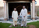 14 April 2013, Karachi, Pakistan: Uzair Baloch (left) stands beside the grandiose pool at his home  in the slum suburb of Lyari, with  Zafar Baloch, General Secretary of PPP district South who was recently shot in the leg at a nearby teahouse.  Lyari is a place out of control and the gangsters running the slum have more support from residents for getting things done than the elected politicians.Karachi is a city wracked by violence and many fault lines that span Taliban infiltration, mafia rackets, sectarian violence and corruption from politicians and security forces. Picture by Graham Crouch/The Australian