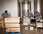 June 18, 2013. Chapel Hill, North Carolina<br />  (left to right) Bottle soy TOPO Gin are labeled, filled, corked and sealed on their way down the assembly line.<br />  TOPO, Top of the Hill Distillery, the brainchild of owner Scott Maitland and Spirit Guide Esteban McMahan, is located in the old N&O Building on Franklin Street. Making gin, vodka and American whiskey from locally sourced wheat, they are one of the few distilleries bringing  organic liquor to ABC shelves around the state.