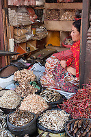 Kathmandu, Nepal.  A Nepali Vendor of Dried Fish, Peppers, Ginger, and Rice Awaits Customers in the Durbar Square Market.