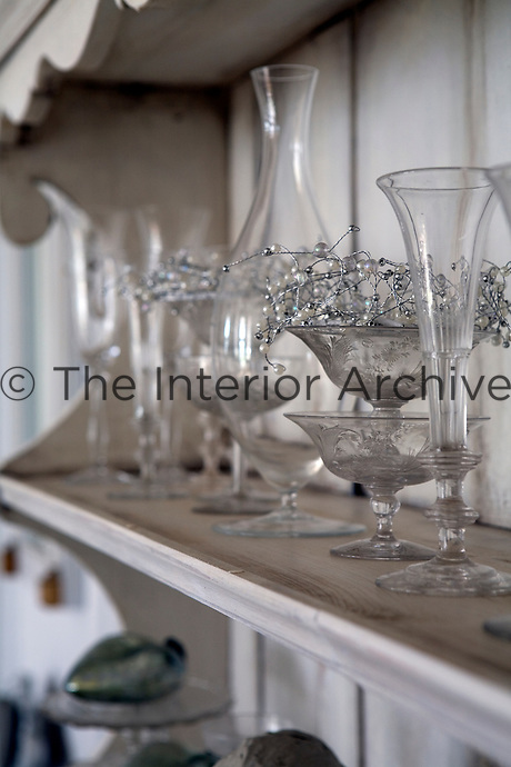 Detail of champagne flutes and glassware on a shelf of the wooden dresser in the living room