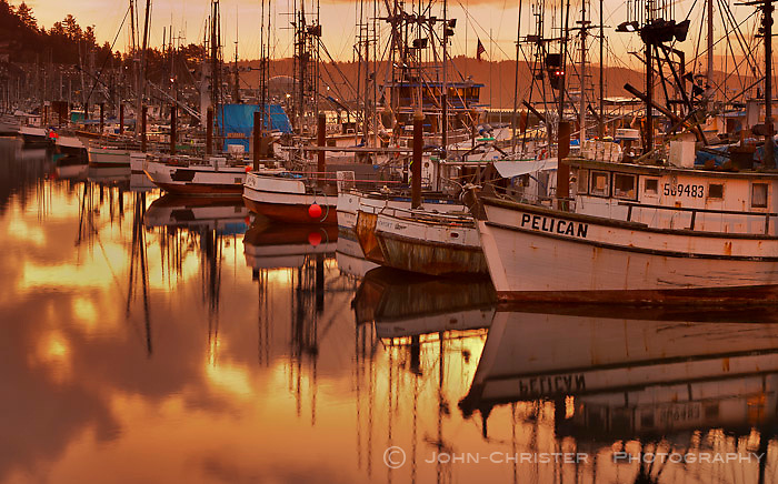 A serenely quiet dawn in Newport Harbor with a warm yellow glow over the harbor.