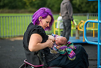 """A mother in a wheelchair breastfeeding her baby in a playground.Image from the breastfeeding collection of the """"We Do It In Public"""" documentary photography picture library project: <br />  www.breastfeedinginpublic.co.uk<br /> <br /> <br /> Berkshire, England, UK<br /> 27/09/2013<br /> <br /> © Paul Carter / wdiip.co.uk"""