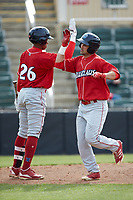 Josh Stephen (right) high fives teammate Malvin Matos (26) after hitting a solo home run against the Kannapolis Intimidators at Kannapolis Intimidators Stadium on April 8, 2018 in Kannapolis, North Carolina.  The Intimidators defeated the BlueClaws 4-3 in game two of a double-header.  (Brian Westerholt/Four Seam Images)